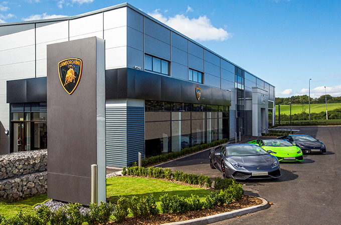 Aston martin kicks off amr production motoring for Car showroom exterior design